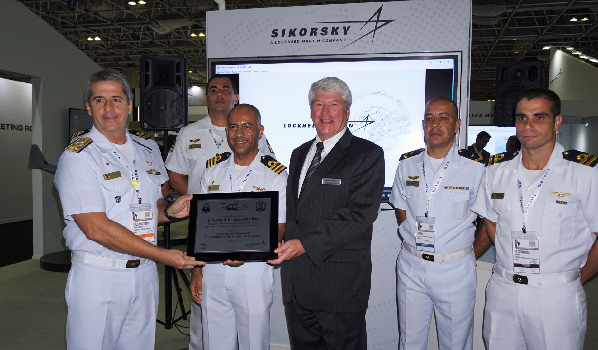 Lockheed Martin's Dale Bennett presents a rescue award plaque to the Brazilian Navy HS-1 squadron during a series of recognition events at LAAD.